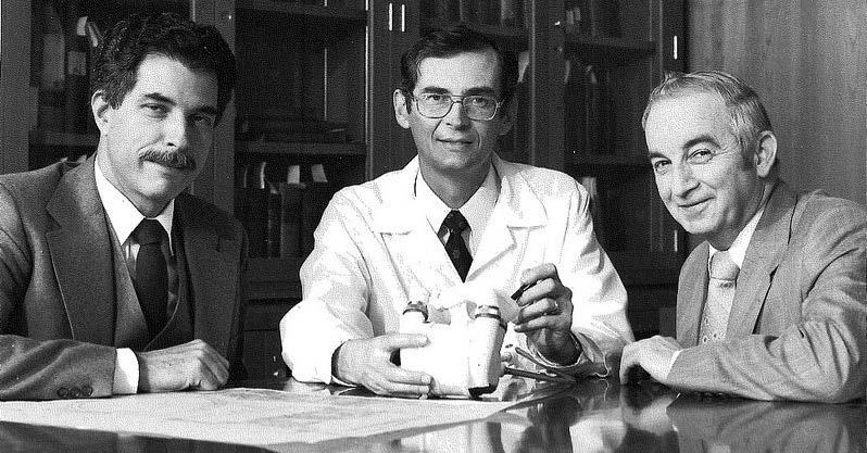 Three members of the interdisciplinary team that developed the heart-assist pump, from left: Gerson Rosenberg, Dr. William S. Pierce, and James H. Donachy (1992). The black-and-white photo shows th ethree men seated at a table with the heart-assist pump on the table in front of them.