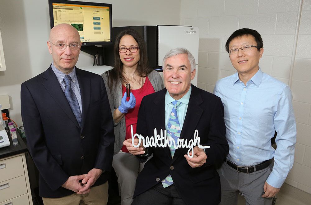 Four members of the Institute for Personalized Medicine are pictured in a lab, including Director Dr. James Broach, third from right. Broach is holding a white sculpture of the word breakthrough. Another researcher in the picture is holding a laboratory sample.