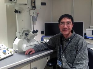 Dr. Han Chen is pictured with Penn State College of Medicine's transmission electron microscope.