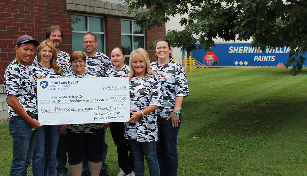 Employees of Sherwin Williams hold a check made out to Penn State Health in 2018.
