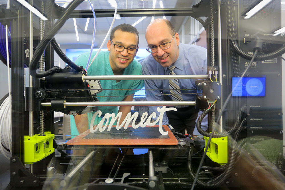 "Two men are pictured looking at a 3D print of the word ""Connect"" in the Technology Sandbox at Harrell Health Sciences Library at Penn State College of Medicine in 2018."