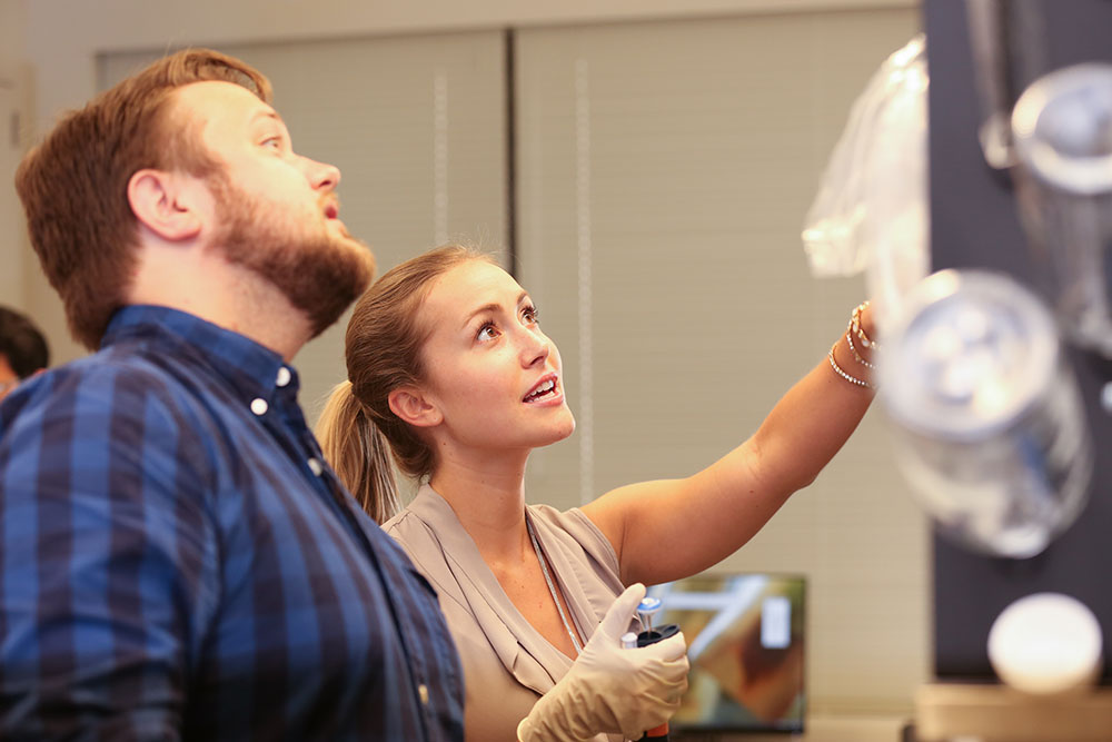 Michael Ludwig and Caitlin McMenamin, both students in the Anatomy PhD Program at Penn State College of Medicine, are seen at work in a lab in the Department of Neural & Behavioral Sciences in 2016. The two are looking downward and framed at right by clean glassware hanging on a lab wall.