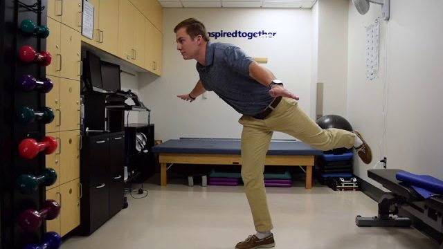 A still from a video shows a person performing the Airplane exercise.