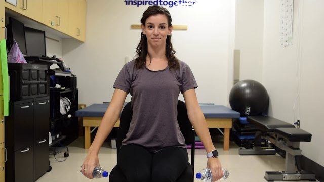 A still from a video shows a person performing the Arm Raises exercise.