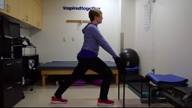 A still from a video shows a person performing the Calf Stretch exercise.