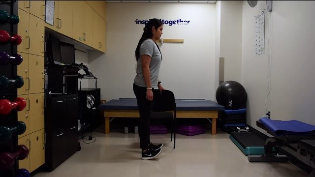 A still from a video shows a person performing the Calf and Heel Raises exercise.