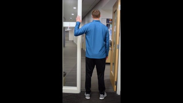 A still from a video shows a person performing the Door Stretch exercise.
