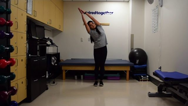 A still from a video shows a person performing the Half-Moon Stretch exercise.