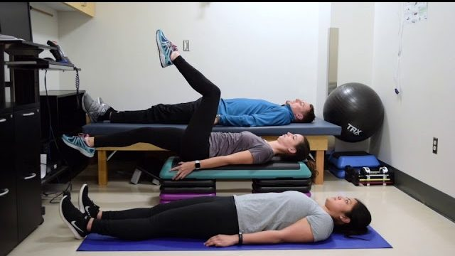 A still from a video shows three people performing the Leg Lift Varieties exercise.
