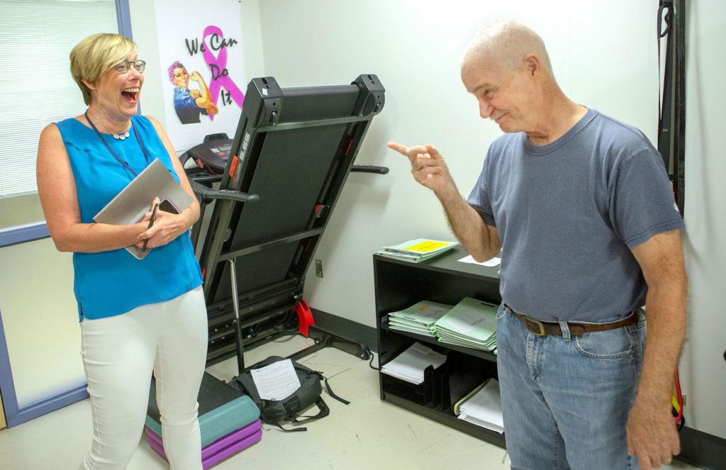 Dr. Katie Schmitz laughs with cancer patient Curt Chambers in the exercise room of Penn State Cancer Institute in 2018. Chambers is pointing at Schmitz jokingly.