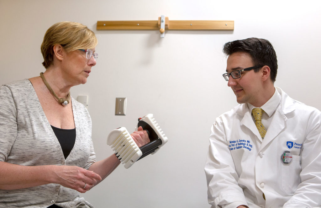 Dr. Kathryn Schmitz talks with Dr. Nicholas Zaorsky in 2019. Schmitz is holding a dumbbell.