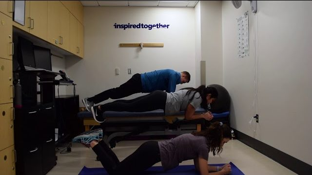 A still from a video shows three people performing the Planks exercise.