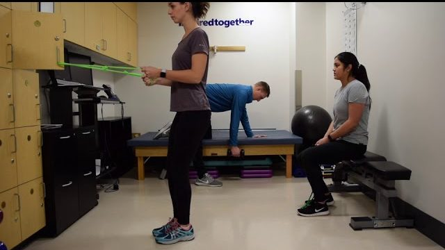 A still from a video shows three people performing the Rows Variety exercise.