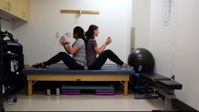 A still from a video shows a person performing the Russian Twists exercise.