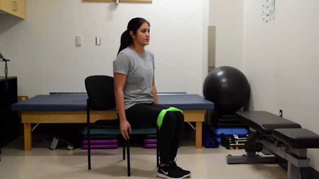 A still from a video shows a person performing the Seated Clamshells exercise.