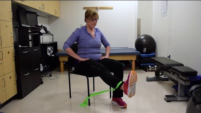 A still from a video shows a person performing the Seated Leg Extension exercise.