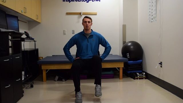 A still from a video shows a person performing the Seated Leg Marches exercise.