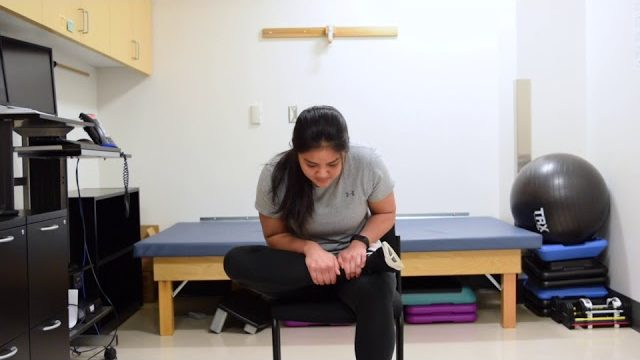 A still from a video shows a person performing the Seated Piriformis Stretch exercise.