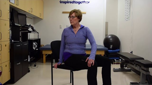 A still from a video shows a person performing the Spinal Twist exercise.