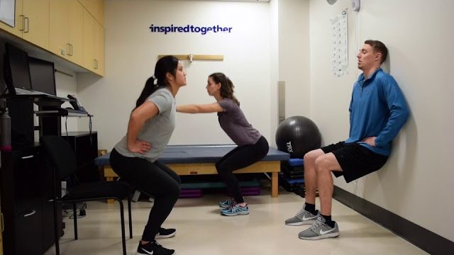 A still from a video shows three people performing the Squat Varieties exercise.