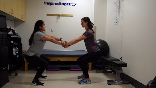 A still from a video shows two people performing the Squats with a Partner exercise.