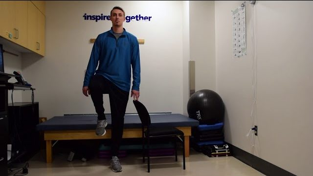 A still from a video shows a person performing the Standing Leg Marches exercise.