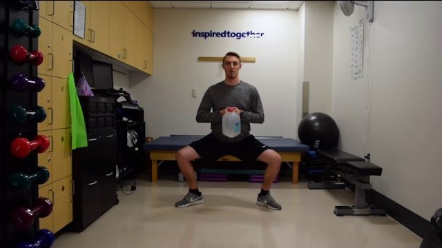 A still from a video shows a person performing the Sumo Squats exercise.
