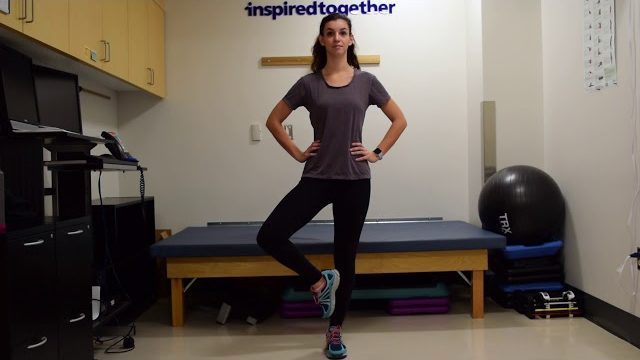 A still from a video shows a person performing the Tree Pose exercise.