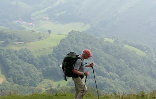 A photo shows a man with a backpack and two hiking poles, walking along a peak with a valley visible beside him. Trees and fields are visible below.