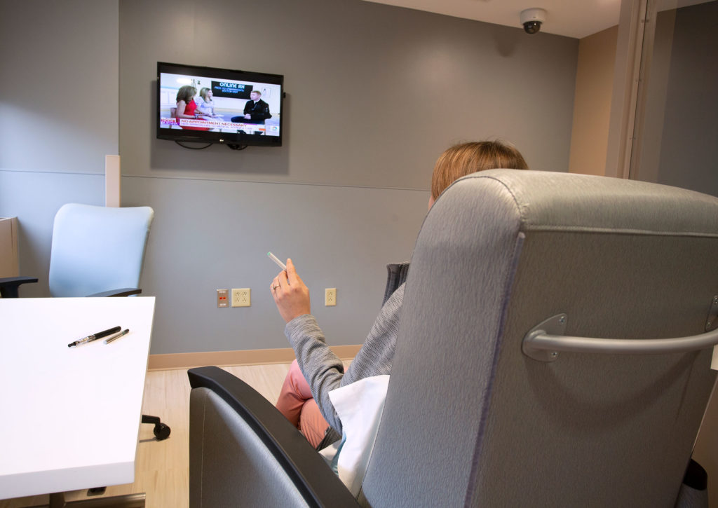 A chair is seen from behind, with a person sitting in it and holding a cigarette. The person is looking at a TV on the wall.