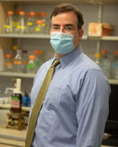 Dr. Matthew Coates standing in his lab with a mask on