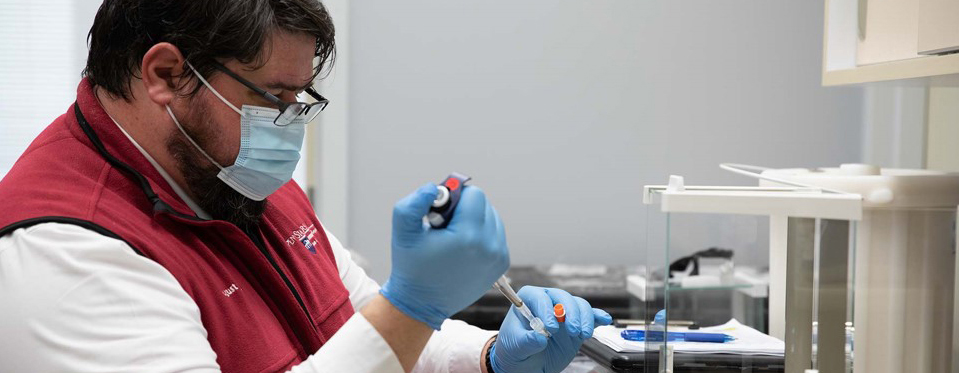 August Stuart, wearing blue gloves and using an injecting tool, works in Dr. Matthew Coates' lab.